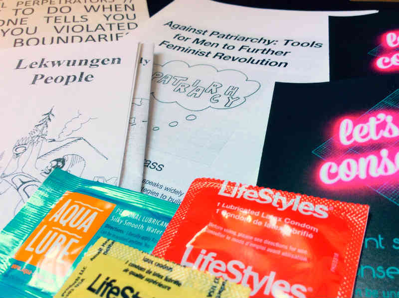 A collection of pamphlets, condoms, and supplies are set out across a UVic table
