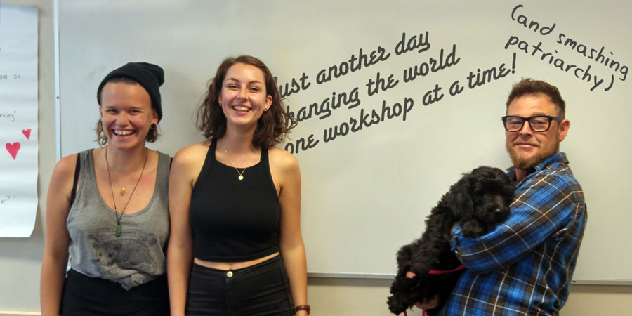 """meg and captain and a participant stand by the whiteboard where it says """"just another day changing the world one workshop at a time!"""