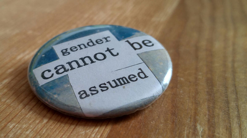 "Close up of a button that says: ""gender cannot be assumed"""