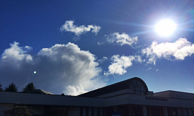 bright blue sky with fluffy white clouds and a shining sun above the student union building