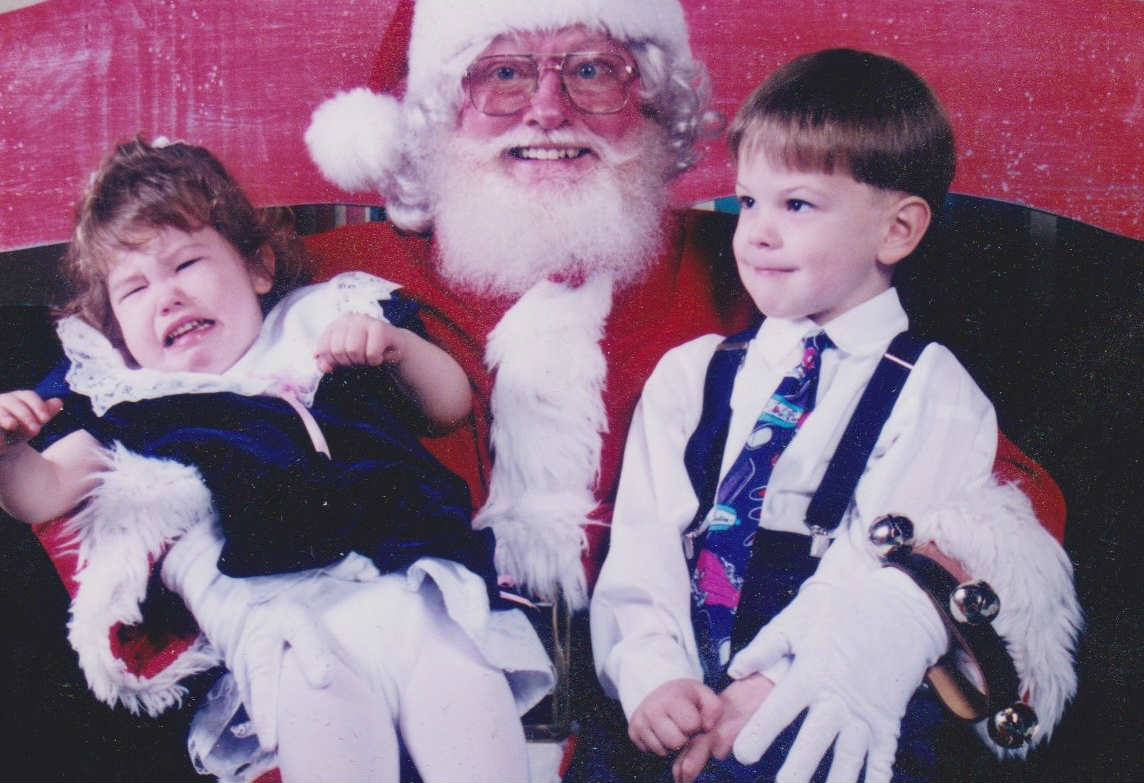 there are two kids sitting on the lap of a slightly creepy santa. santa has a weird smile and massive 70's glasses. the one kid is crying and struggling to get out of santa's lap, she clearly does not want to be there. the second child doesn't seem as bothered.