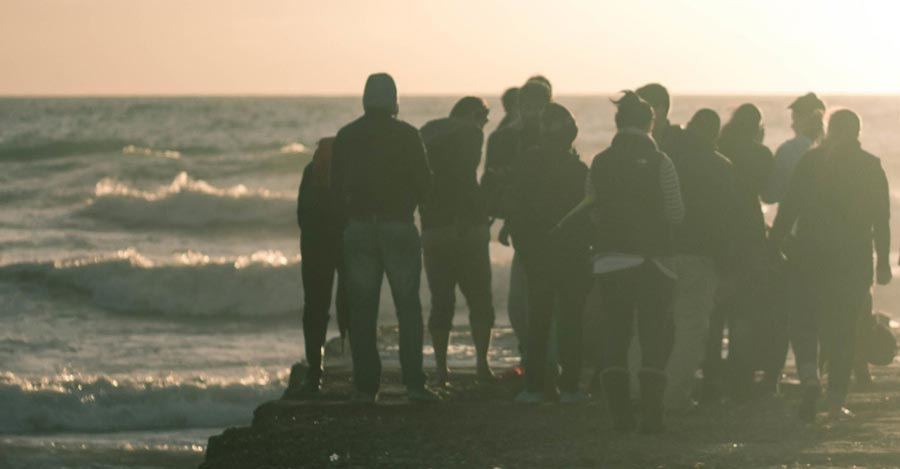 People are congregating on a breakwater watching the waves come in and standing together in community.