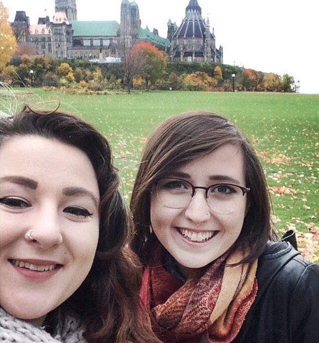 Kenya and Paloma taking a selfie in front of the Parliment buildings in Ottawa. The leaves are yellow and the two are wearing scarves for the chilly fall weather.