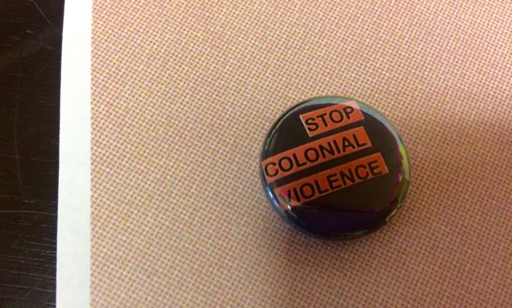 "button that says ""stop colonial violence"""