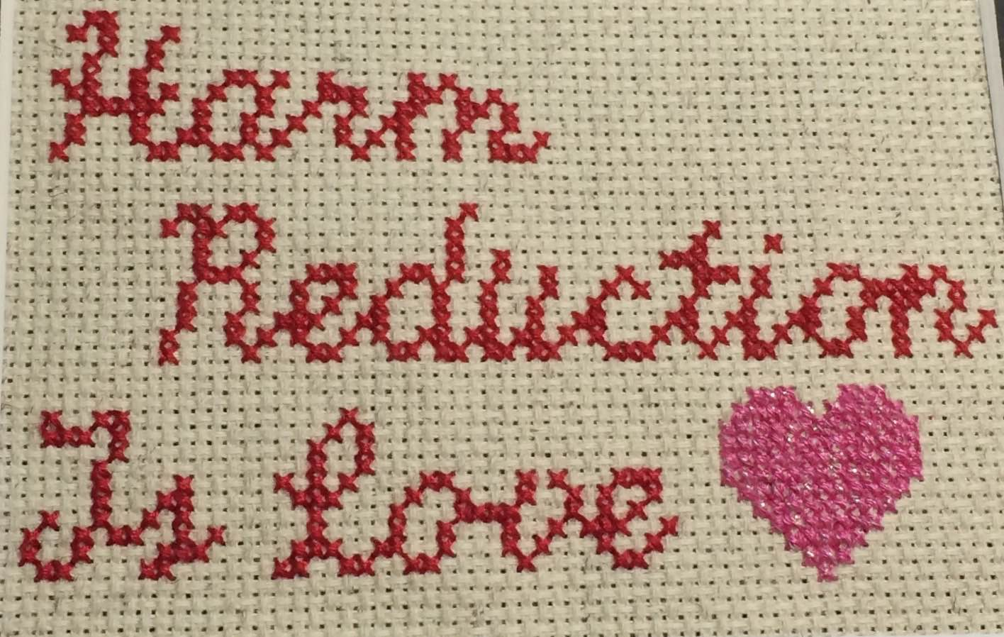 "Cross-stiched red handwriting that says ""harm reduction is love"" followed by a pink heart"