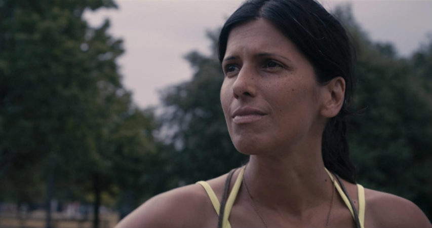 Attiya Khan looks into the distance, with blurry everygreen trees in the background. She squints against the light. Attiya Khan is the co-director of the film and her story is the basis of the documentary