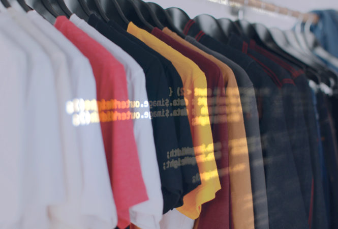 Image of t-shirts on a clothing rack, with a second graphic of computer code layered over top.