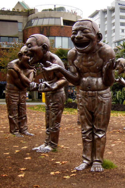 """Photo of """"A-maze-ing Laughter"""" sculpture by Yue Minjun. Sculpture features laughing bronze men in various comedic poses. Photo taken by Paul Lloyd."""