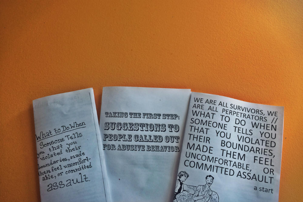 Photo of three zines discussed in this blog post against an orange wall.