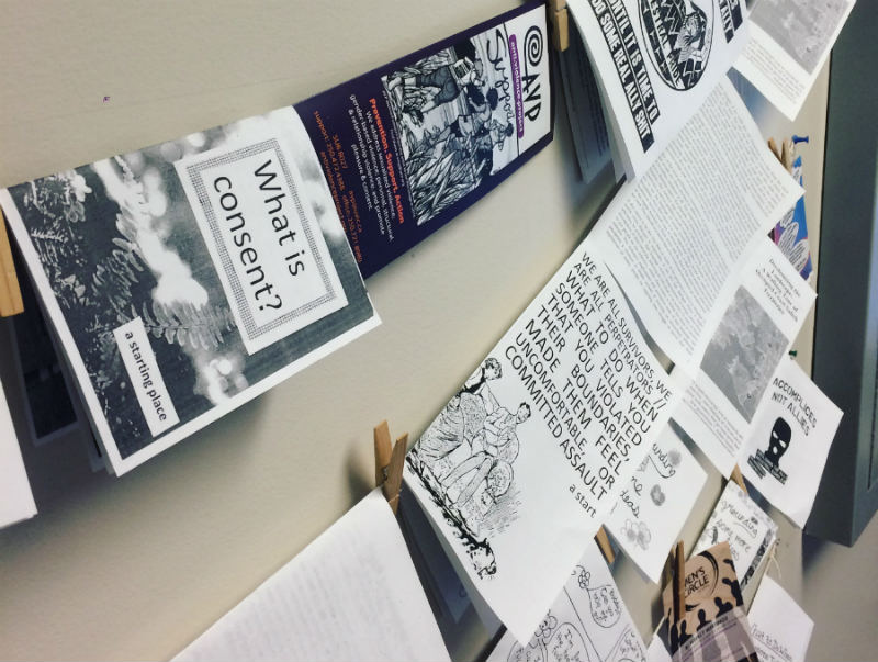 Photo of strands of zines hung up against a wall.