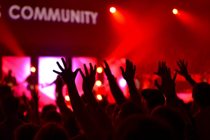 "Image of crowd with outstretch hands, and the word ""Community"" on a sign in the background."