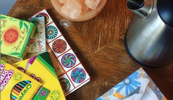 Photo of a table with several items on it including a kettle, a box of kleenex, colouring supplies and a salt lamp.