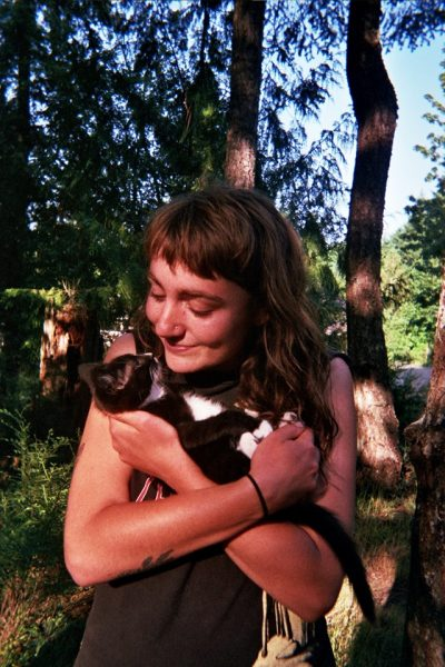 Image of Alida Kelly holding a kitten while standing in the forest.