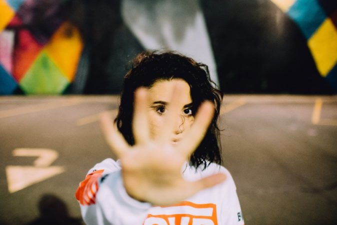 "Image of a person with their hand extended out in front of them with their fingers spread out as if to signify ""stop"" or ""no."" Behind the person is in parking lot that has colourful walls"