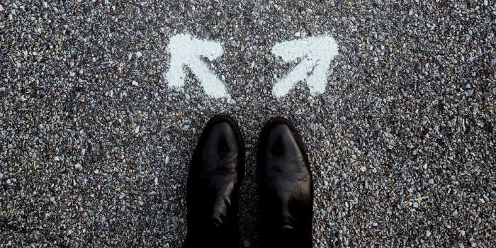 Photo taken of a person's feet in black shoes. In front of the shoes are two arrows painted on the cement that are pointing left and right.
