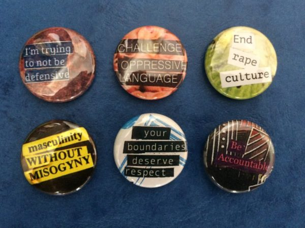 """Six pin back buttons with the phrases """"I'm trying to not be defensive,"""" """"Challenge oppressive language,"""" End rape culture,"""" Masculinity without misogyny,"""" """"your boundaries deserve respect,"""" and """"Be accountable"""""""