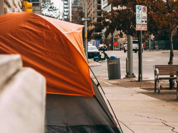 Image of an orange tent set up on a sidewalk, downtown in a city.