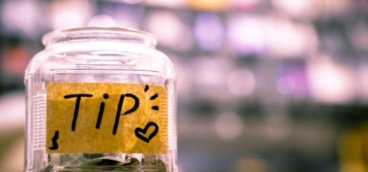 Photo of a tip jar filled with money