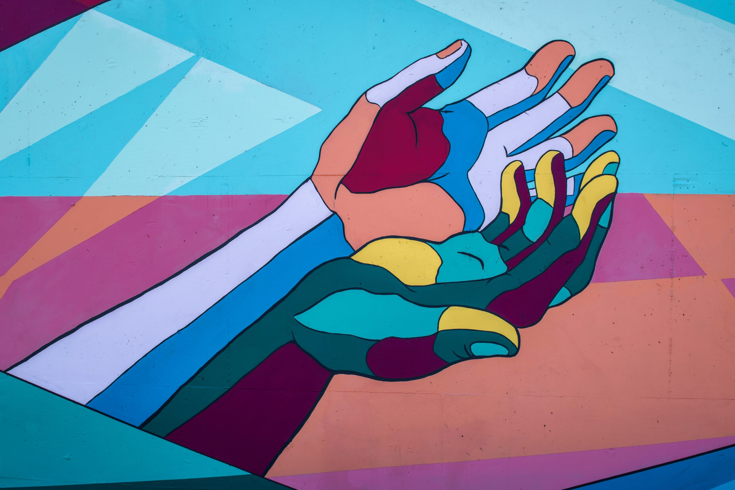Graphic of a red and blue abstract hand being held by a green, yellow and red hand, with blue and pink blocky shapes in the background.