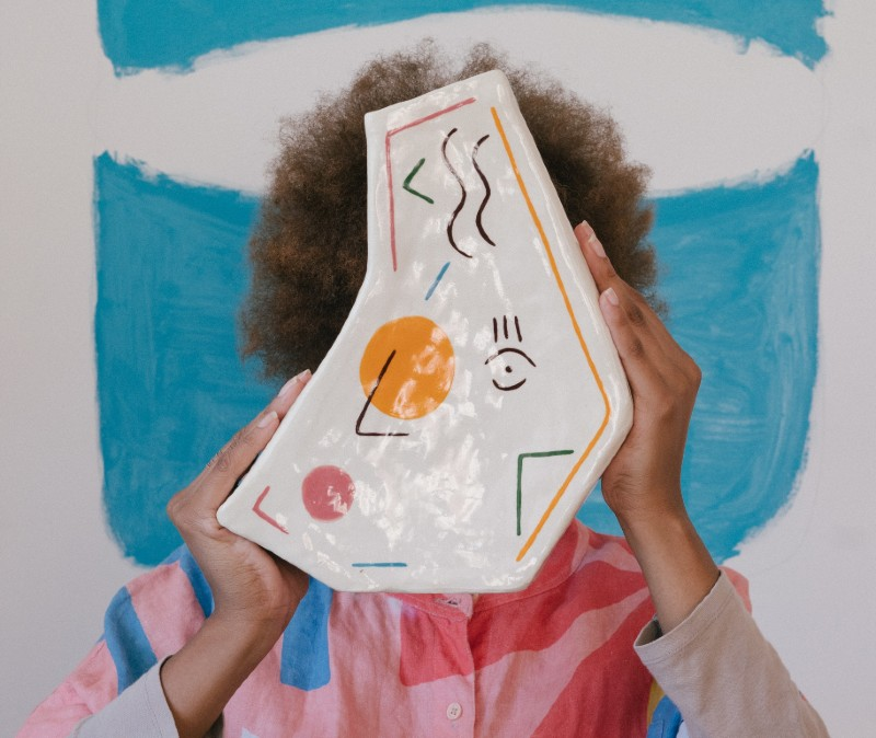 A person with curly brown hair stands against a blue and white painted background. They are wearing a pink and blue geometric patterned shirt. The person's face is covered by a colourful ceramic piece of art they are holding in front of them.